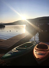 two kayaks and a boat in the water next to the dock on the beach at the sundowner on lake george with the sun rising over the lake george water and adirondack mountains