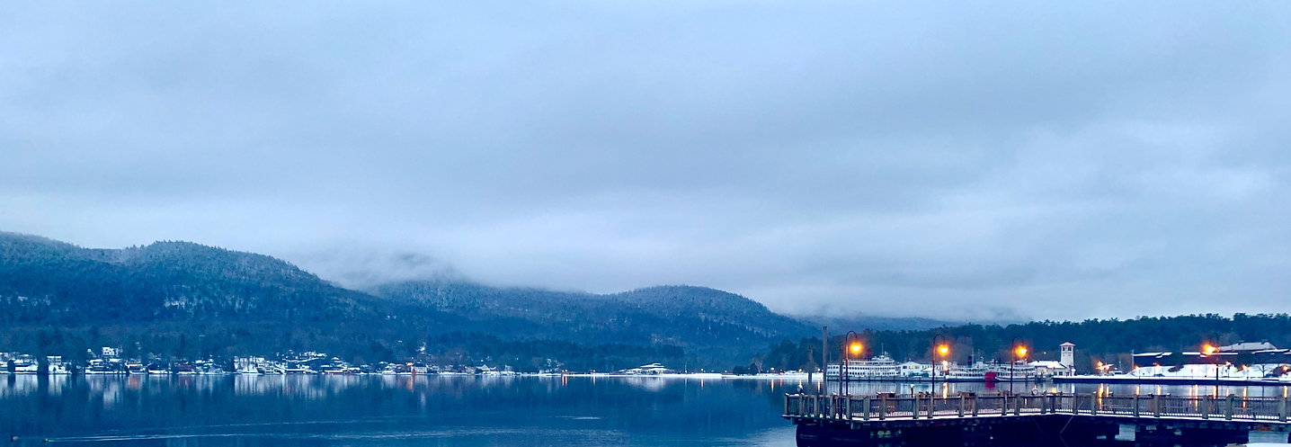 overcast early winter evening over lake george with the adirondack mountains in the background and the dock off of shepard's park in lake george