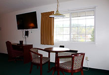 Table and chairs and wall mount large screen television in king room at the sundowner motel in lake george new york