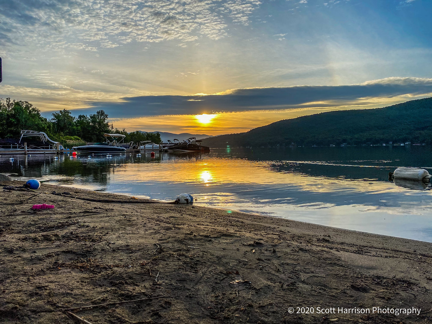 sunrise over the lake george water from the beach at the sundowner on lakeg george with the adirondack mountains in the background