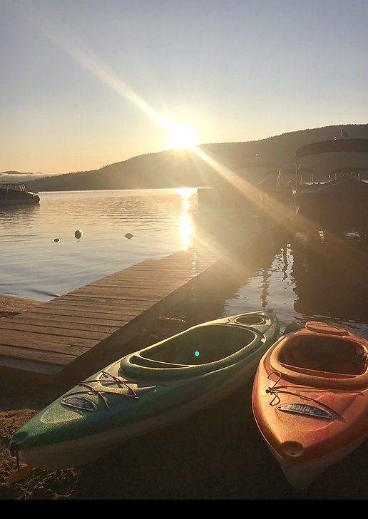 Kayaks and a dock on Lake George at sunset with the Adirondack Mountains in the background