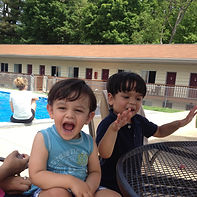 Two childrens smiling and laughing by the pool at the Lake George Motel Montreal