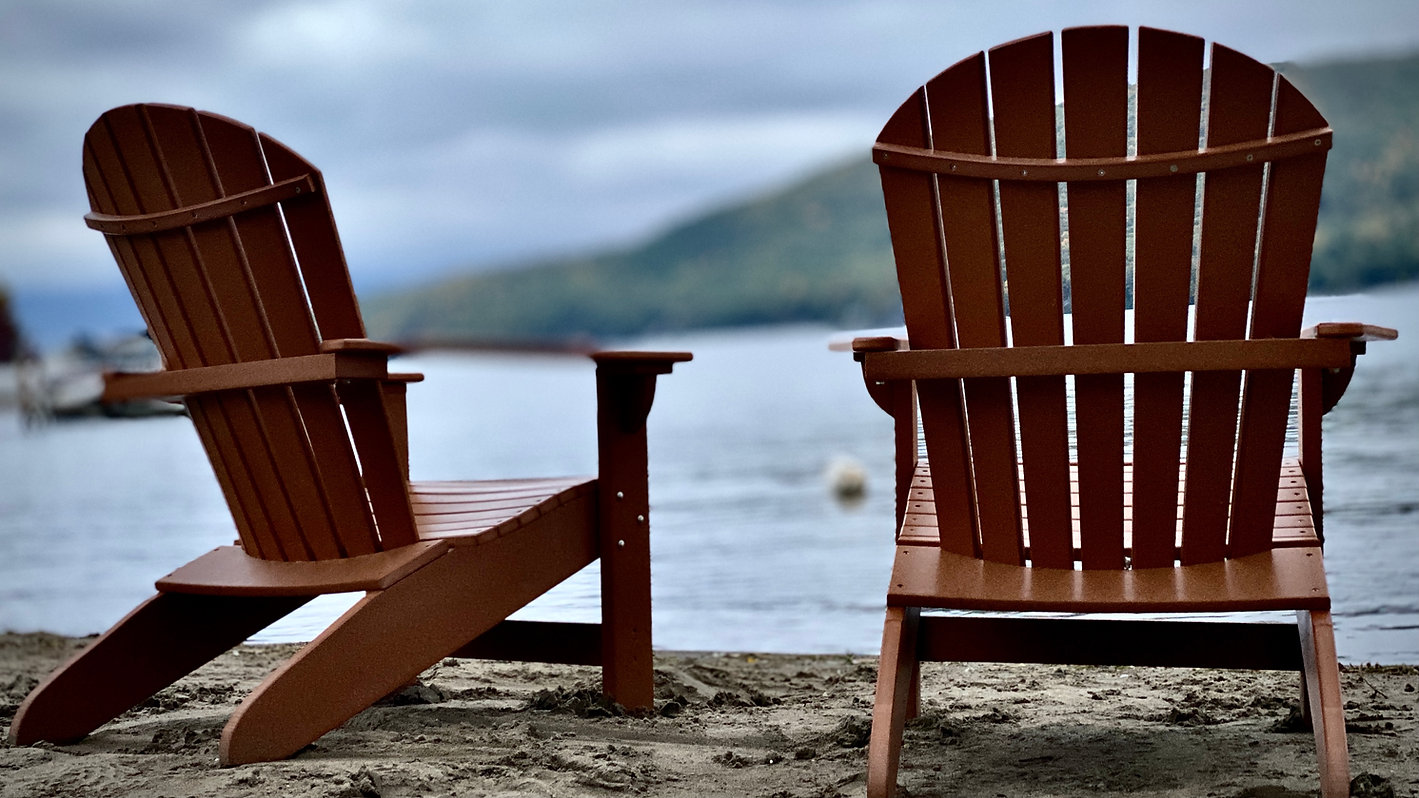 two adirondack chairs on the beach at the sundowner on lake george with a blurred view of lake george in the background