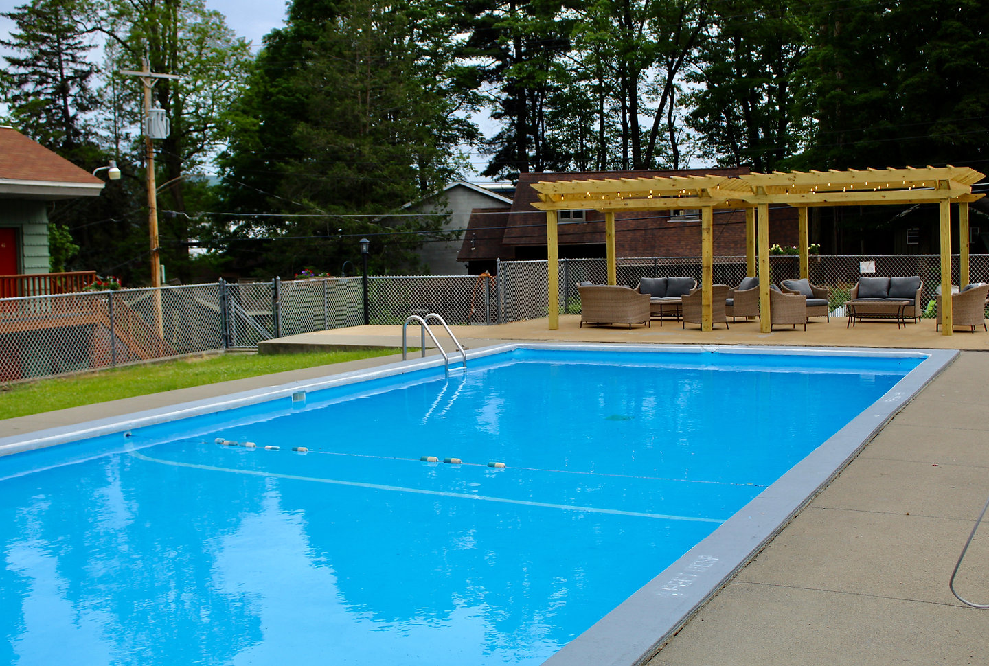 Swiming pool and sundeck with pergolas at the lake george motel montreal at 3 lake avenue in lake george ny