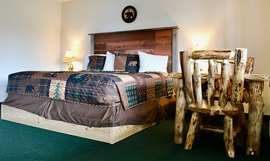 Lakeside hotel room with a king size bed and handmade furniture  at the sundowner on lake george