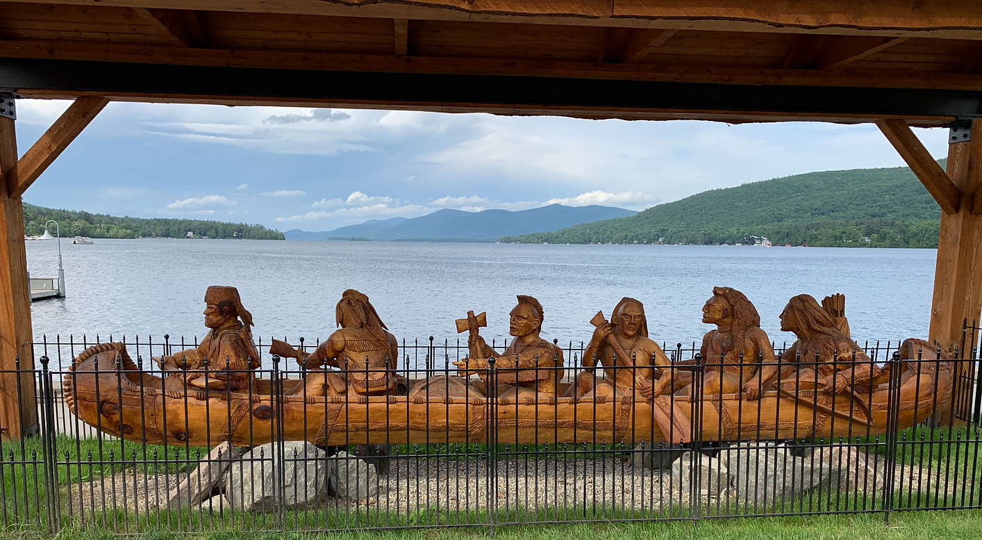Wooden carving of Mohicans in a canoe with Lake George and the Adirondack Mountains in the background