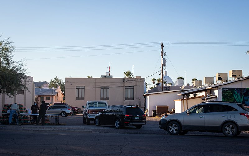 The sun begins to set over Ajo as cars line up behind the Ajo Farmers Market & Cafe to pick up free bags of food.