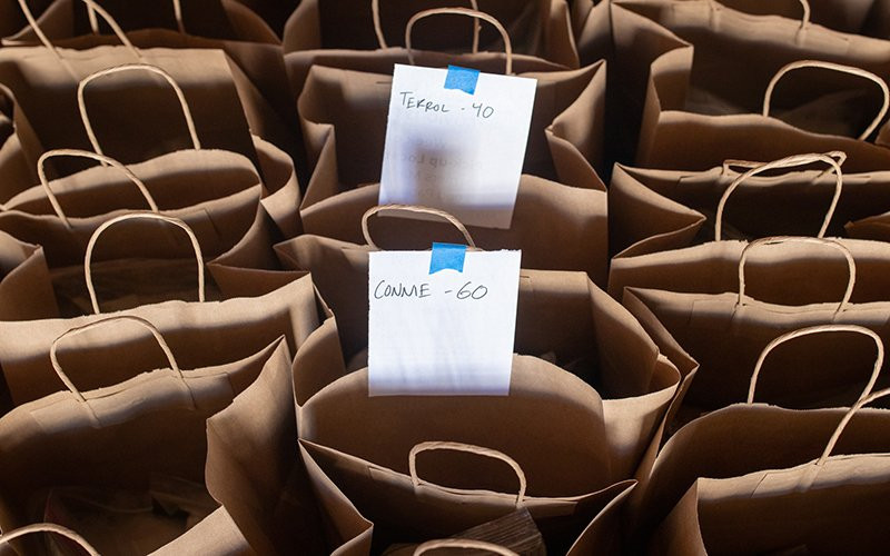 Paper bags filled with food are lined up and ready for distribution by the Ajo Center for Sustainable Agriculture. Each contains a combination of flour, sugar, salt, oatmeal, rice and beans. Each week, the center gives out 600 to 800 bags and boxes of food to residents of Ajo and the Tohono O'odham Nation.