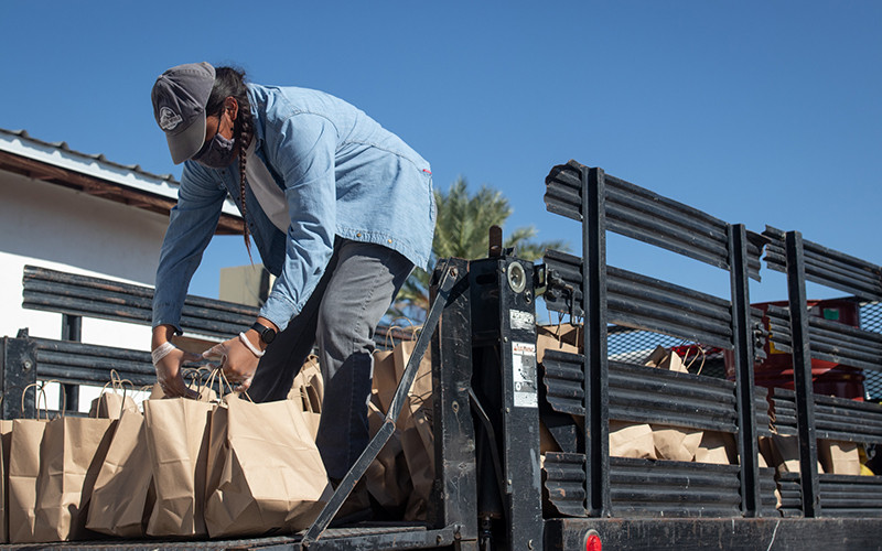 Isaiah Nez loads bags of food onto a truck bound for the Tohono O'odham Nation. The food bought and collected by the Ajo Center for Sustainable Agriculture is distributed to hundreds of families on the reservation by tribal representatives.