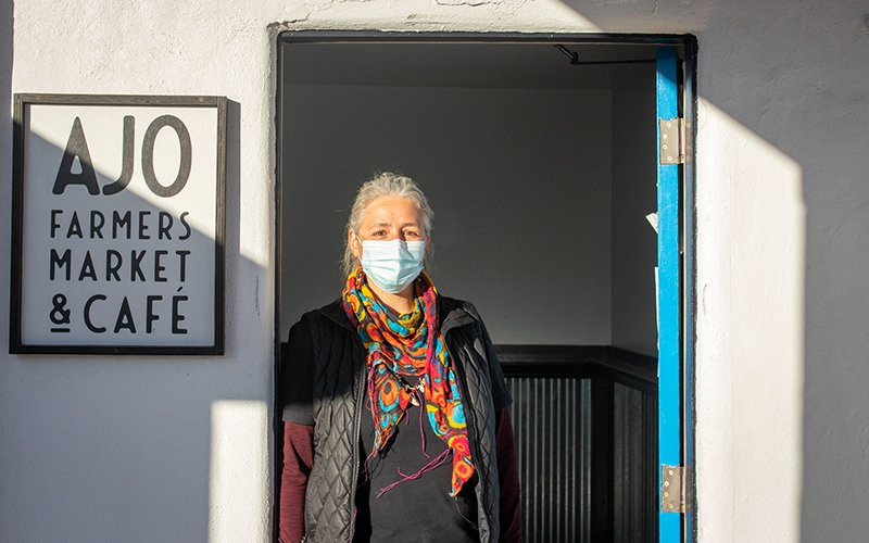 "Nina Sajovec stands in the back doorway of the Ajo Farmers Market & Cafe, which has housed Ajo Center for Sustainable Agriculture's COVID-19 food relief operations since April. ""We're pulling hundred-hour weeks,"" she says."