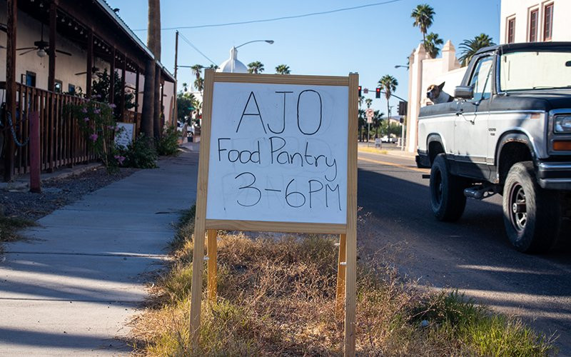 A sign in front of the Ajo Farmers Market & Cafe advertises the Ajo Food Pantry, which was overwhelmed with demand early in the pandemic. On designated afternoons, people can come by and pick up bags of food for themselves and their family and neighbors.