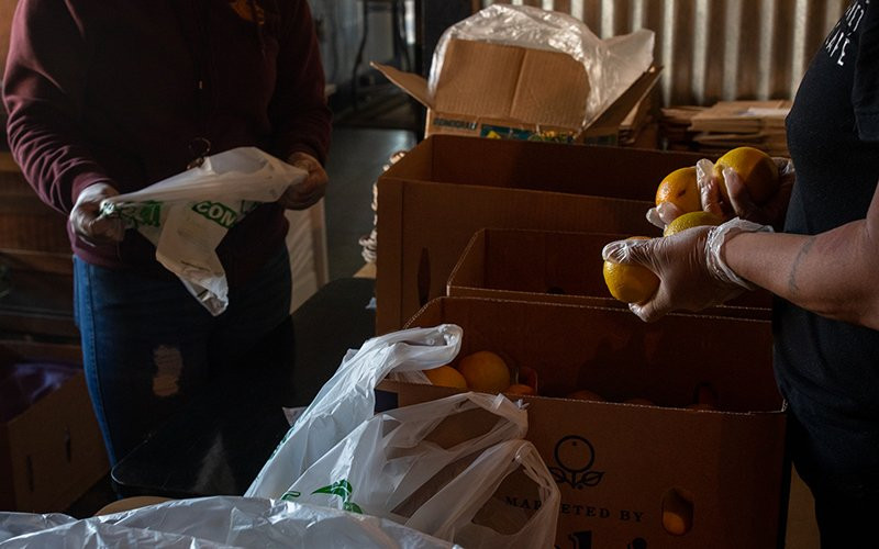 Volunteers with the Ajo Center for Sustainable Agriculture sort through boxes of oranges to be distributed to families in need in Ajo and the Tohono O'odham Nation. Nina Sajovec, the center's director, says fresh fruit and vegetables are the items most requested by families because they're the hardest to get.