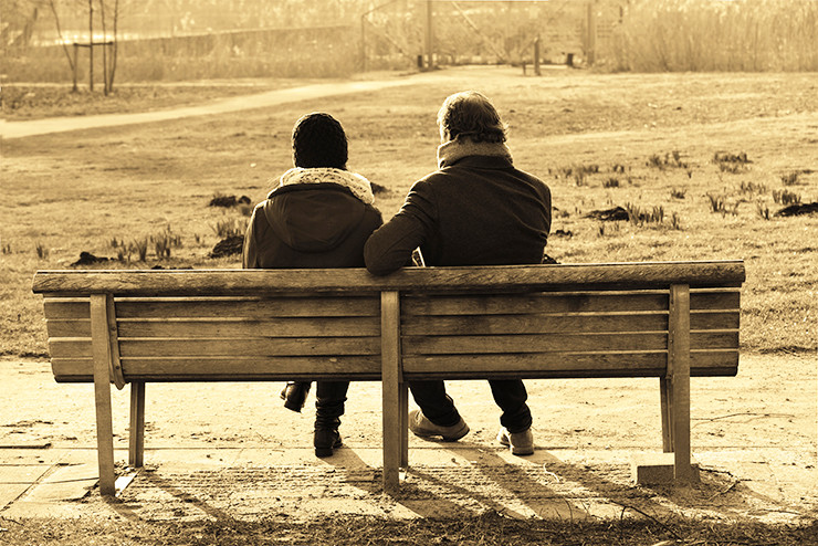 a couple talking on a park bench