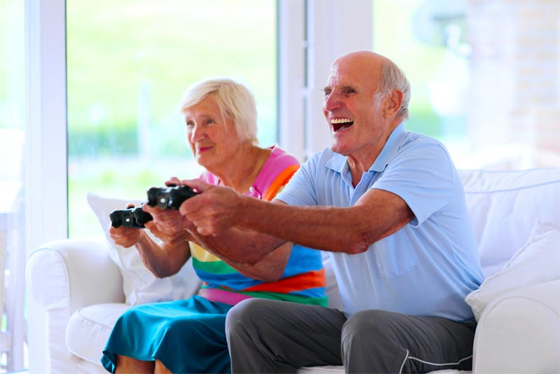 Seniors laughing and playing video games