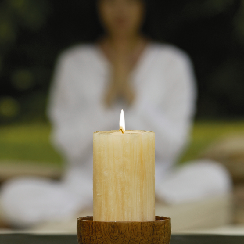 burning candle in the foreground and an out of focus person meditating in the background