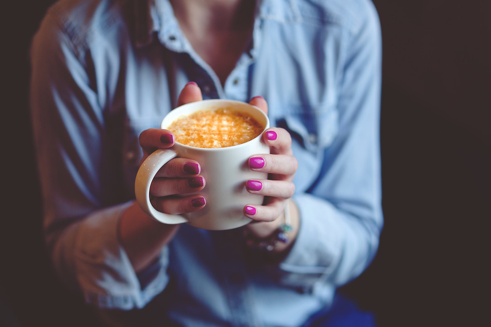 person with pink fingernails holding a cappuccino