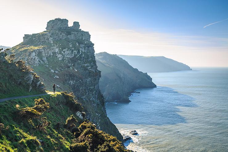 person standing on cliffs overlooking ocean