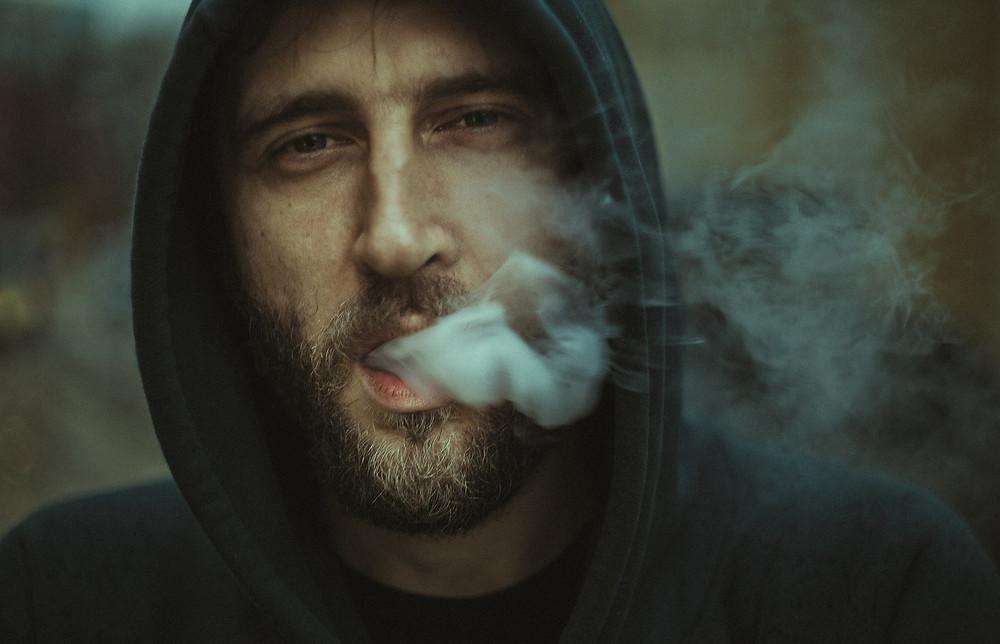 bearded man in a hoodie blowing smoke
