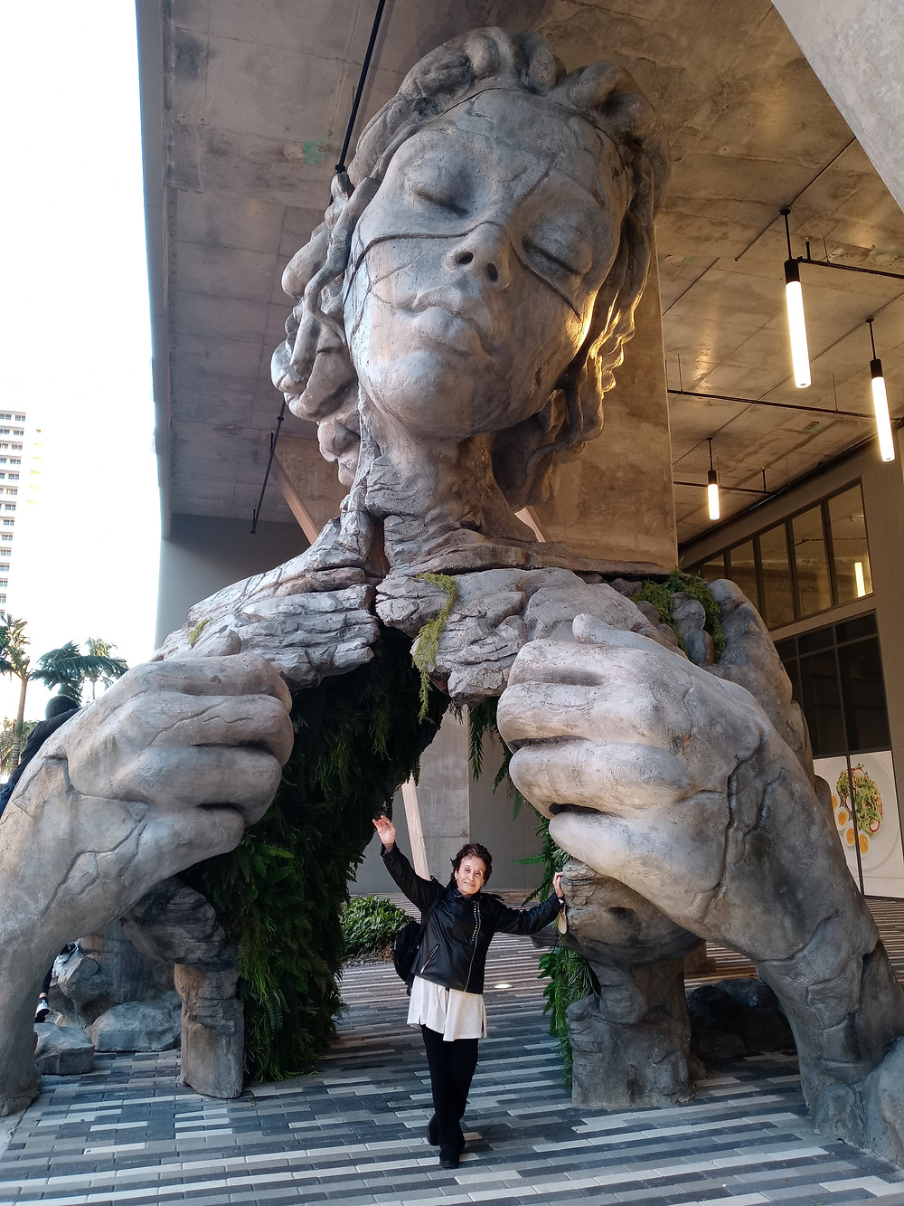 Nomi Bachar leaning against a stone statue of a woman
