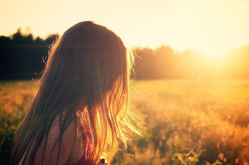 Girl with hair covering her face standing in a field with sun shining as it sets