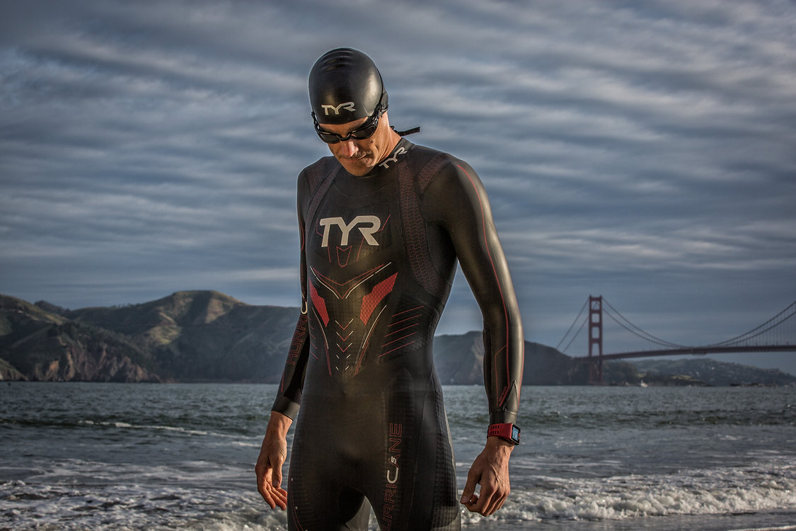 Andy Potts stands outside the Golden Gate Bridge in TYR wetsuit and gear