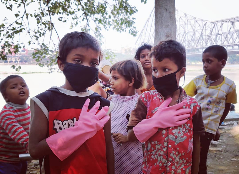 Volunteer kids with hand gloves and mask ready to clean
