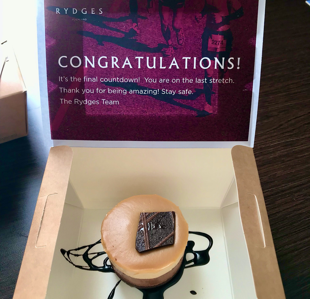 Fancy cake in a box with a card saying 'Congratulations you're on the last stretch. Thank you for being amazing. Stay safe, the Rydges team