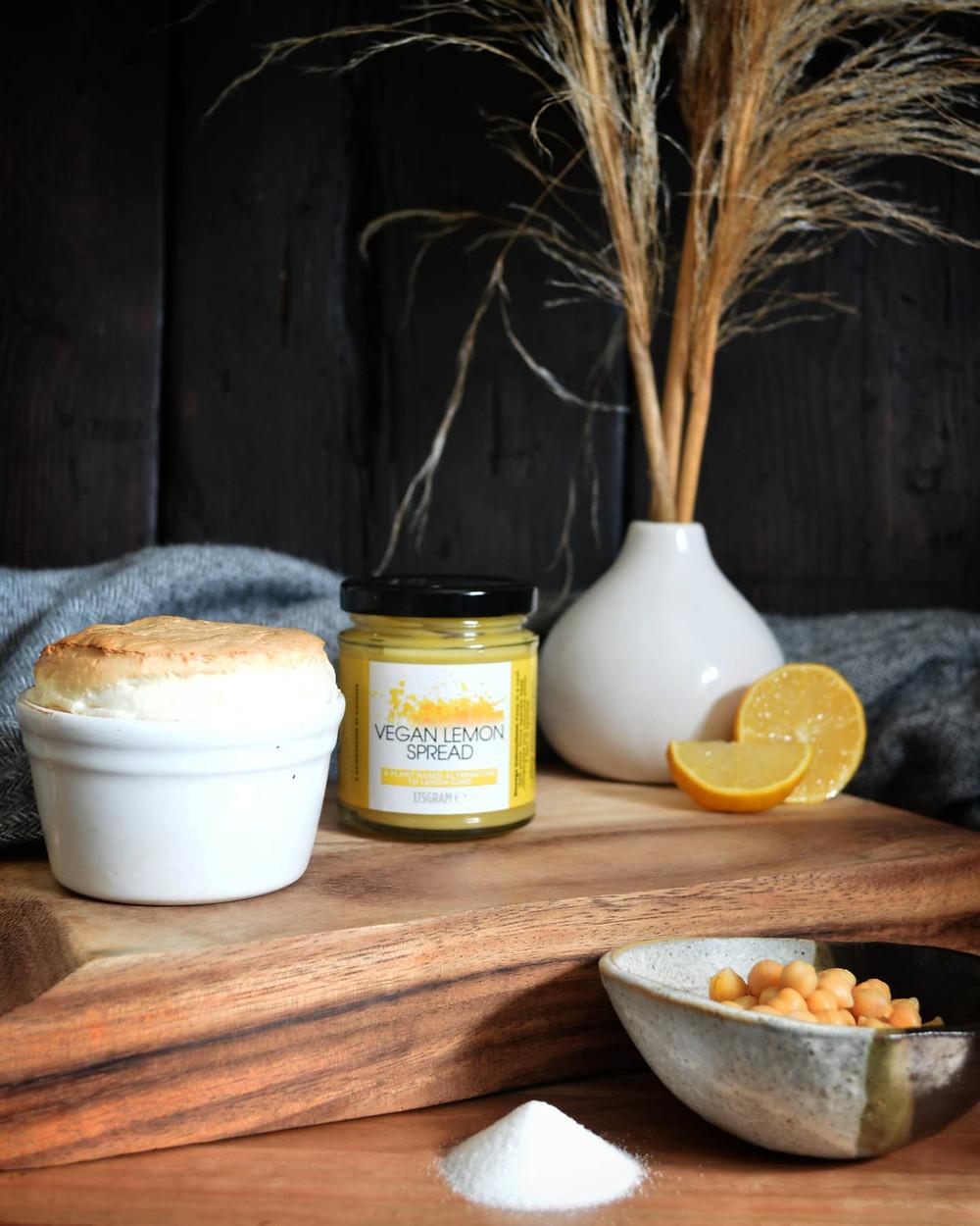 Vegan lemon soufflé pictured with Janda Food's jar of lemon spread, a freshly sliced lemon, chickpeas and sugar.