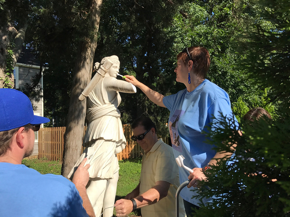 Adopt a Monument committee and volunteers cleaning a sculpture.