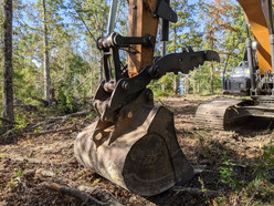 Excavator with thumb attachment that will be used to stack trees into a pile for milling at a later date.