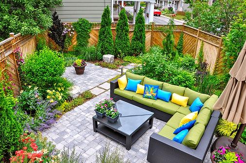 A beautiful small, urban backyard garden featuring a tumbled paver patio, flagstone steppi