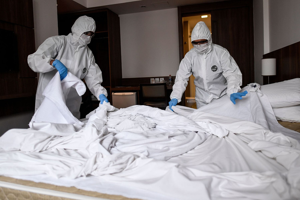 two men cleaning a hotel room in personal protection equipment kit