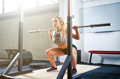 Woman doing squats with barbell at the c