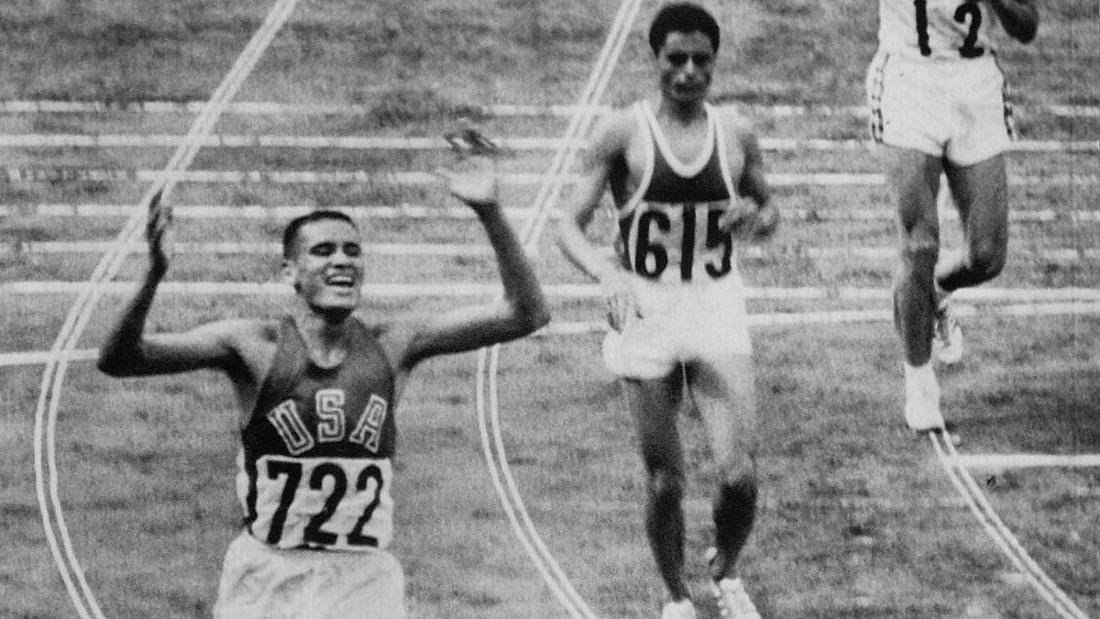 While Al Oerter was tending to his injury, Billy Mills, his Kansas teammate, wins the 10,000m race