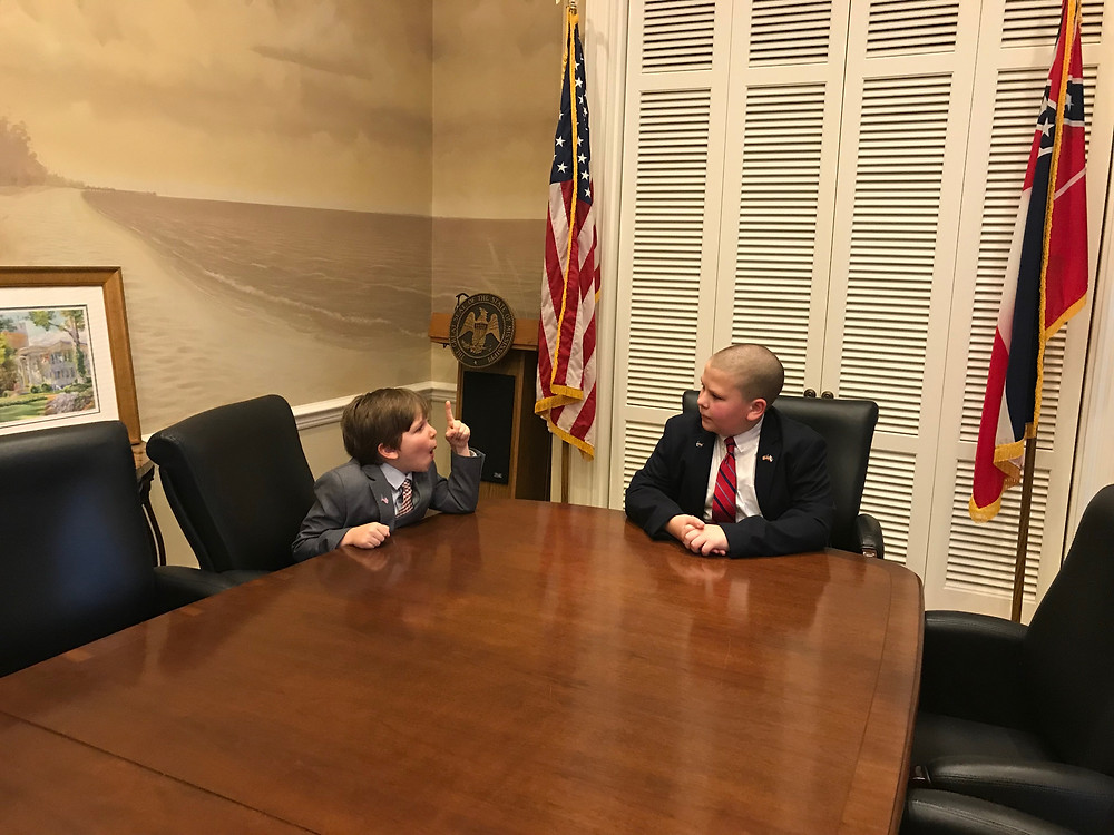 Future state leaders Eli and Landon (Representative Ashley Henley's son sitting in the Governor's board room arguing future matter of state.