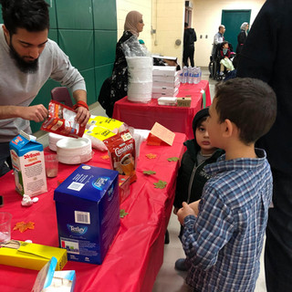 Two young boys stand near a refreshment table at a SMILE event.