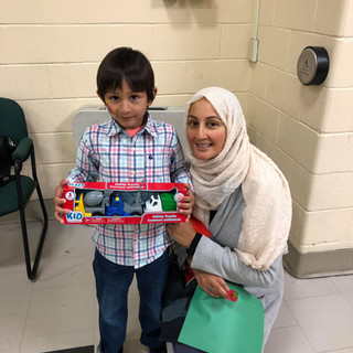 A young boy holds new toy cars, he is beside a smiling woman who is crouching down next to him and smiling.