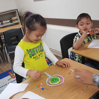 Two young children sit at desks as they do arts and crafts