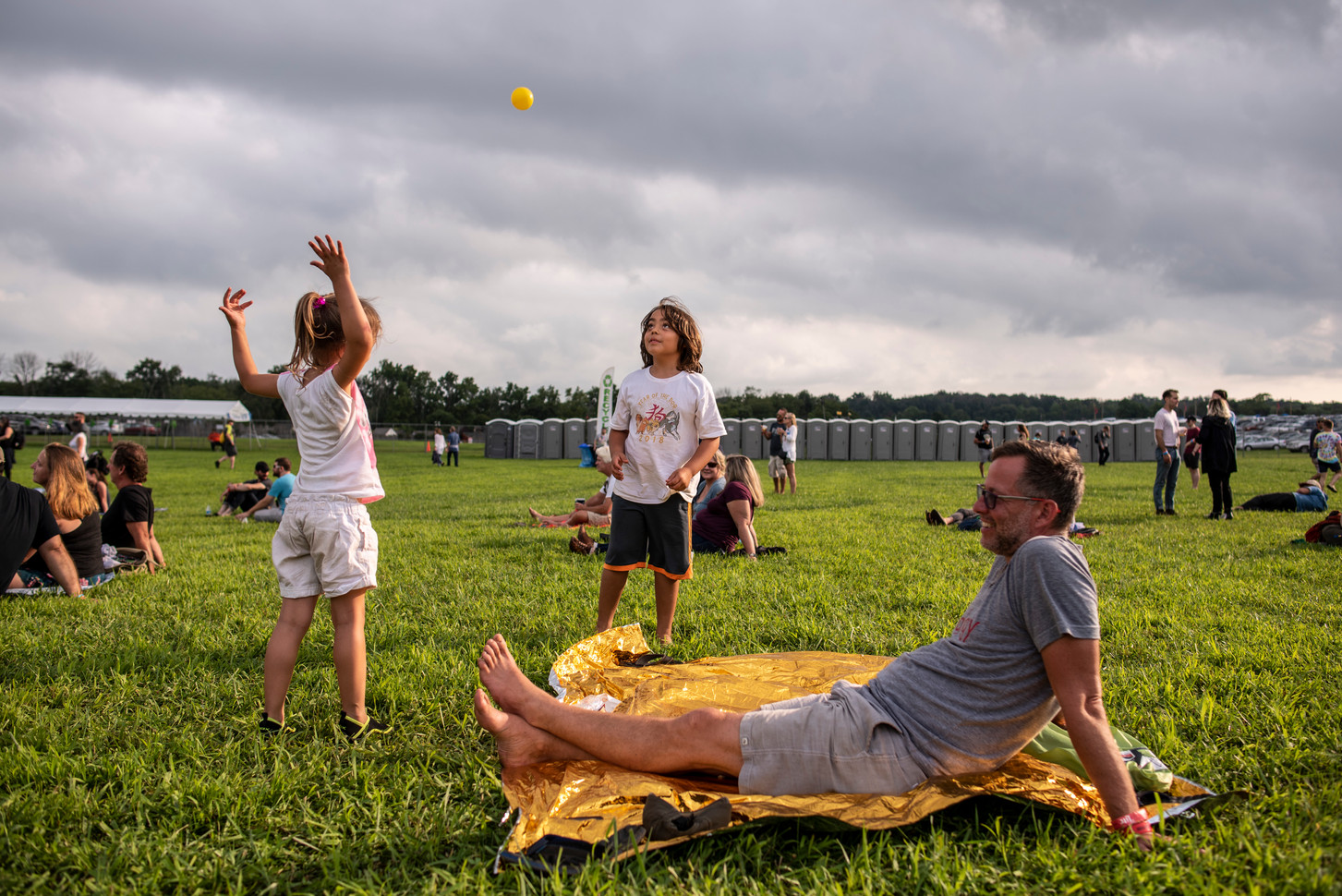 Two young kids toss a ball while their dad sits, waiting for the next band to begin playing at Bellwether Music Festival.