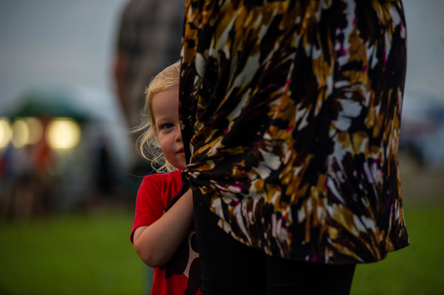 A young girl hides behind her mom after being scolded for running away.