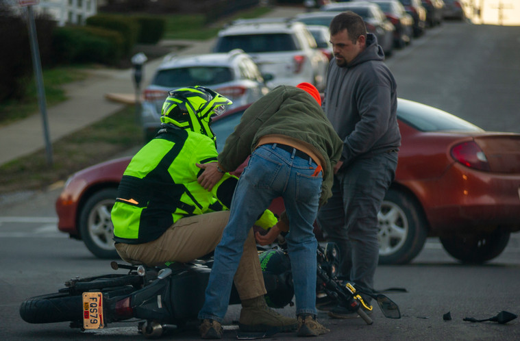Bystanders help a motorist who was just involved in a crash during the county wide blackout in Athens, Ohio, on Friday, Jan. 22, 2021.