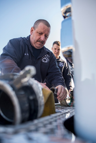 Greg Thesing (left) and Josh Veldhaus (right) checking the fire hose on the front of the truck on Thursday, March 15, 2018. Thesing always knew he wanted to be a firefighter and has been chasing the fires for 26 years.