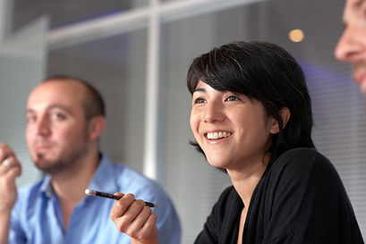 woman with pencil at confeence and man in background