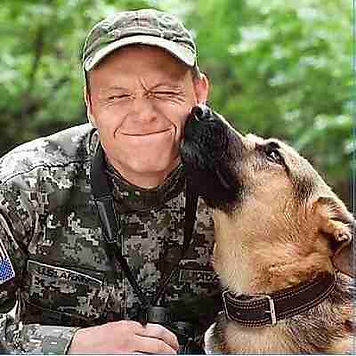 Military man with dog licking face