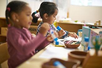 Girls in classroom glueing