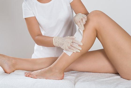 Beautician Waxing Leg Of Woman With Wax