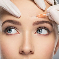 Portrait of young Caucasian woman getting cosmetic injection of botox in forehead. Beautif