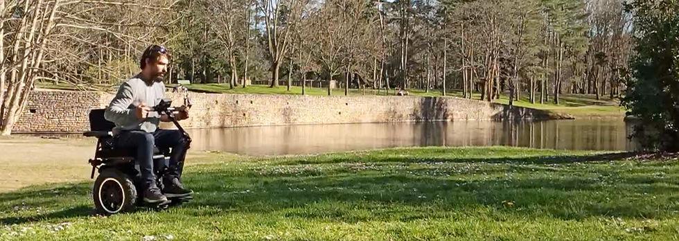 Philippe traverse la pelouse sur le GUS au bord d'un lac dans un parc.