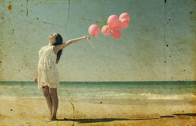 Young pregnant woman holding red balloon