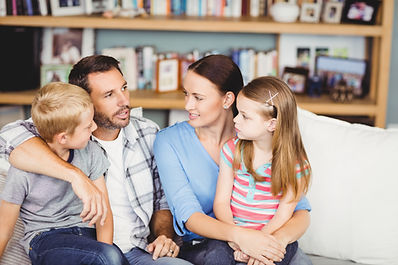 Close-up of family discussing on sofa in